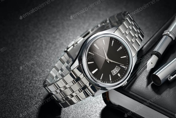 Steel wristwatch on black background