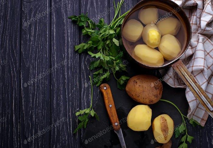 Uncooked peeled potatoes on dark background