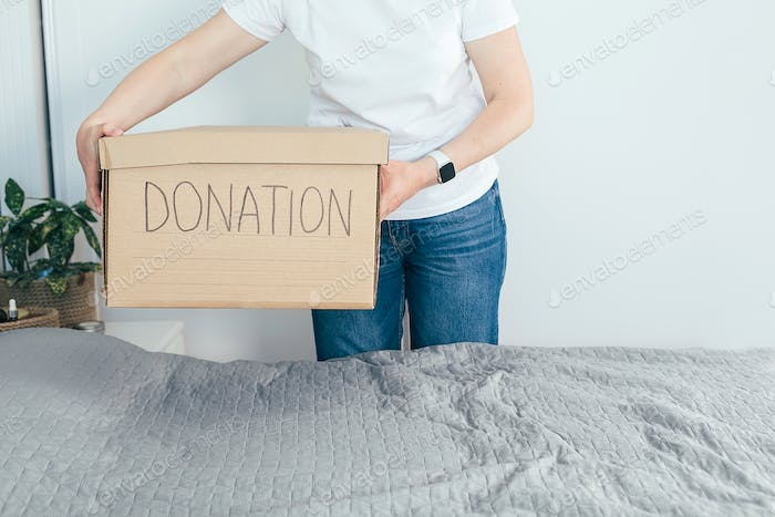 Woman holding donation box with clothes and personal items. Domestic life, lifestyle