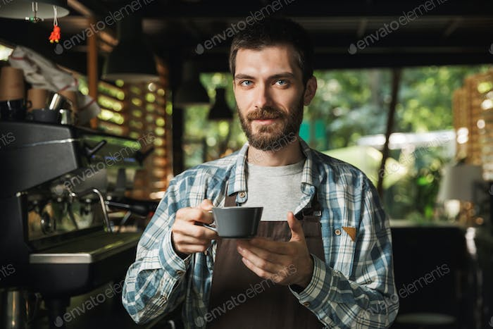 Portrait of brunette barista man holding cup of coffee while wor
