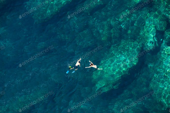 Couple snorkeling in the sea. Above view