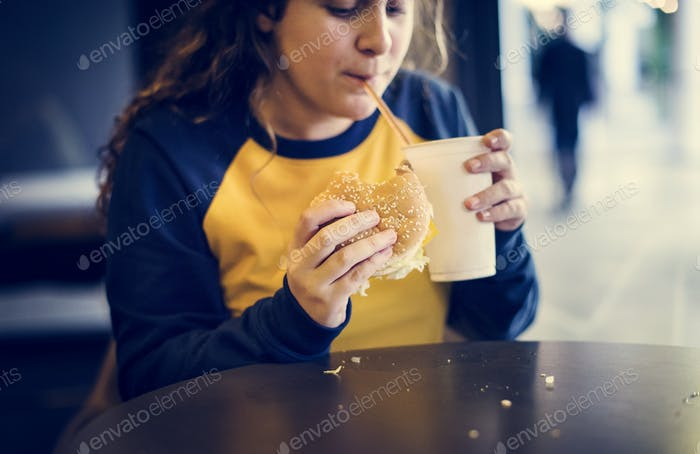 Close up of teenage girl eating hamburger obesity concept