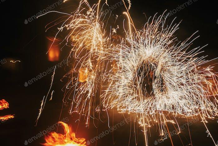Feuertänzer schwingen, Feuer drehen und Mann jonglieren mit hellen Funken in der Nacht