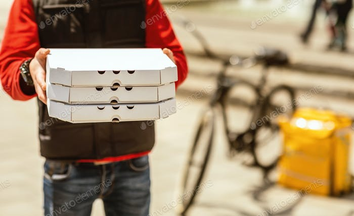 Unrecognizable Courier Offering Pizza Boxes Standing Near Scooter Outside, Cropped