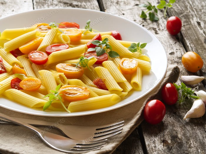 Penne pasta with tomatoes and basil on old rustic gray wooden background, low-calorie diet