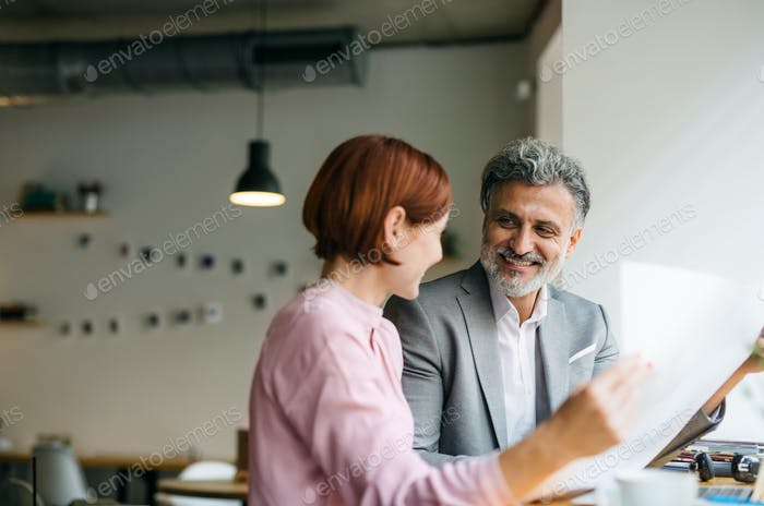 Man and woman having business meeting in a cafe, looking at blueprints.