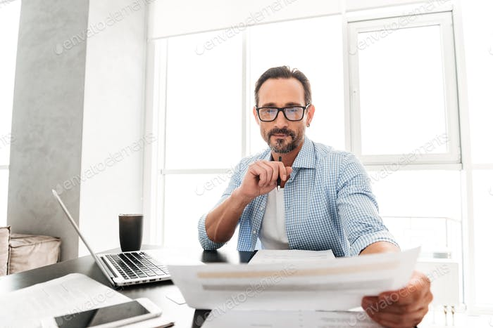 Smart mature man working with documents