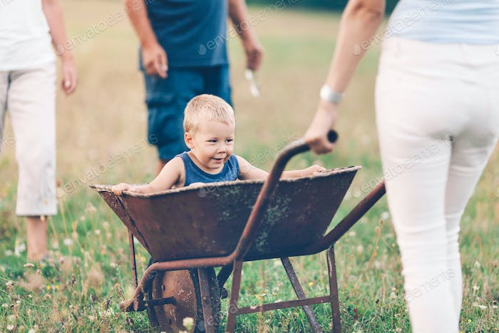 Family Pushing Their Small Child In A Wheelbarrow Photo By