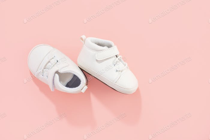 Baby shoes on pink background