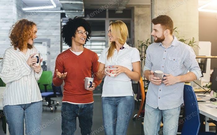 Friendly colleagues enjoying coffee in modern office