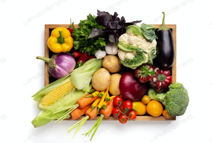 Fresh organic vegetables in wooden box on white