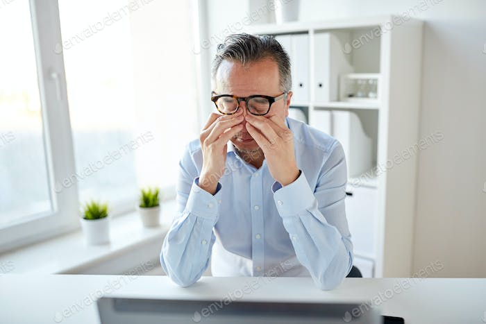 tired businessman in glasses with laptop at office