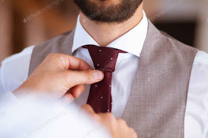 Closeup of two hands helping with the tie to a groom at his wedding