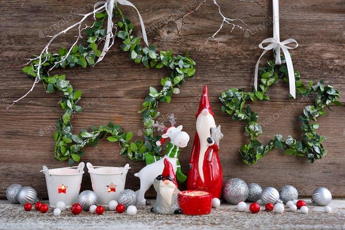 Weihnachtskomposition mit Zwergen, Elchfigur und festlichen Dekorationen auf hölzernem Hintergrund