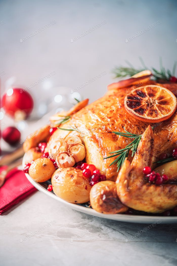 Roasted chicken with festive decoration, candles, light bokeh on concrete background. Traditional
