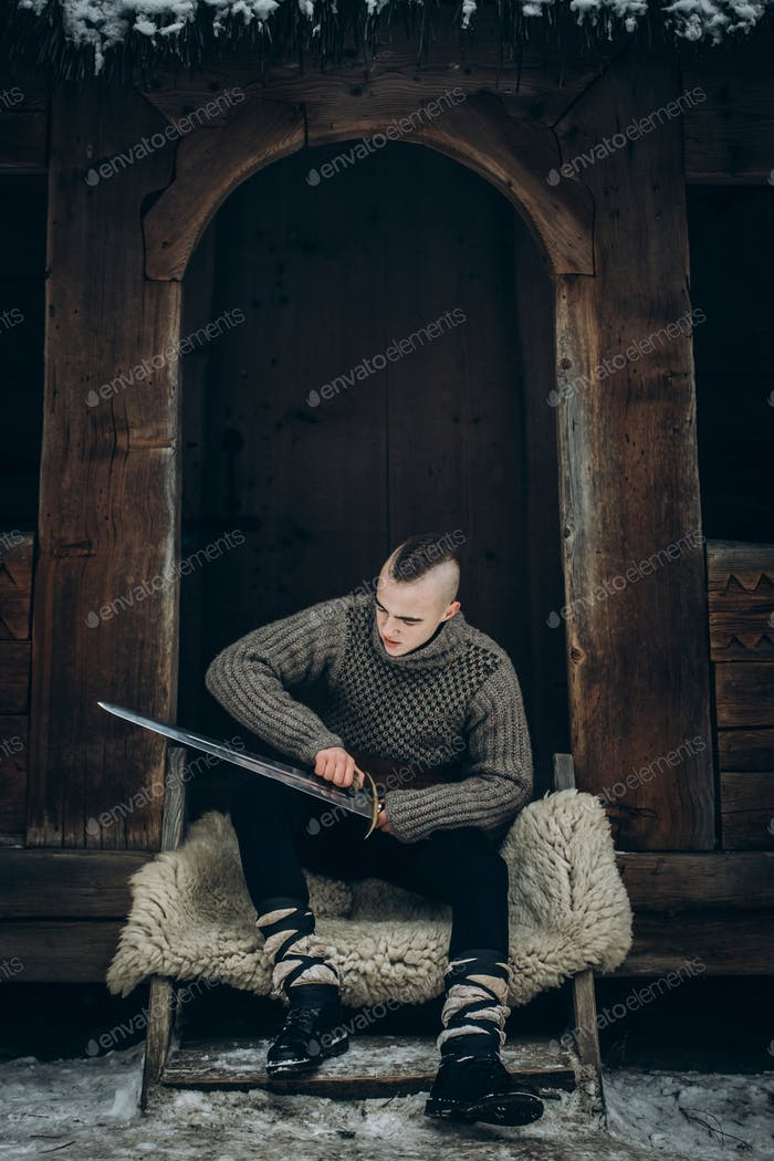 Portrait of strong viking warrior sharpening his sword, scandinavian viking cosplay