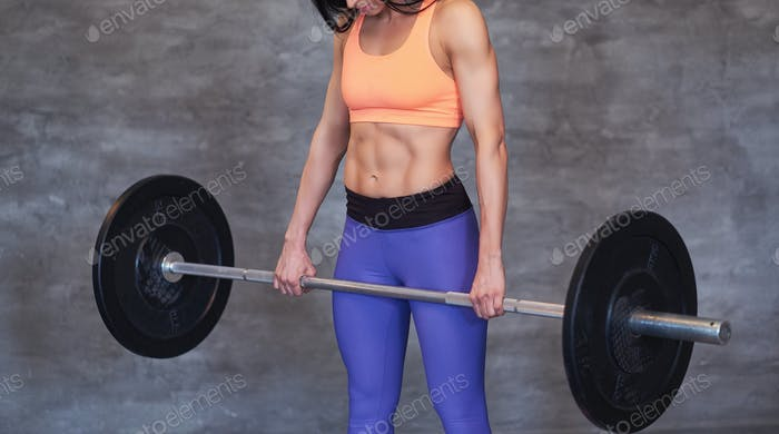 Portrait of a strong brunette sporty woman in a sportswear doing exercise with a barbell at the gym.