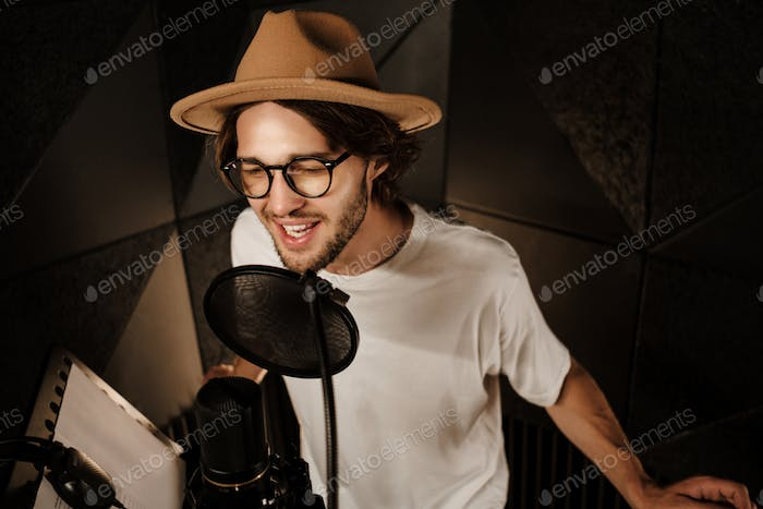 Attractive stylish male musician singing in microphone recording song in professional studio