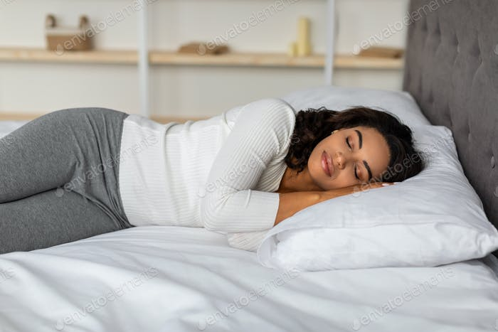 Mujer joven afroamericana durmiendo en la cama