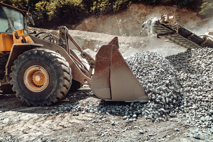 Wheel loader machine unloading rocks in the open pit mine and ore quarry
