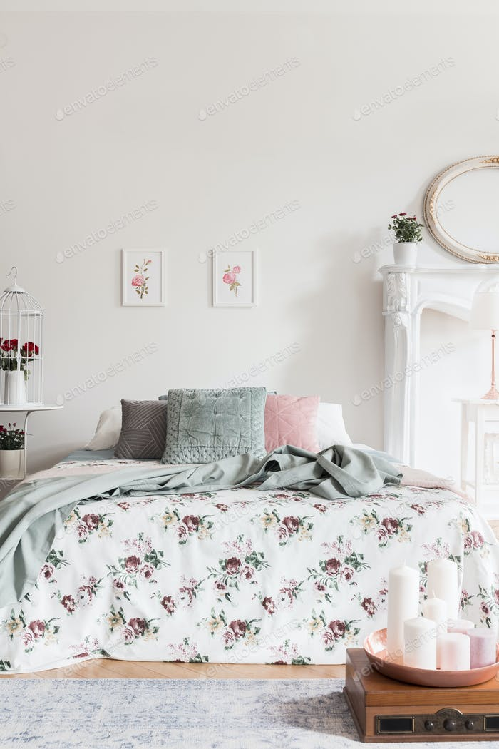 A comfortable bed with a rose pattern coverlet and fluffy pillow
