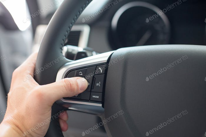 Male hand uses car steering wheel controls