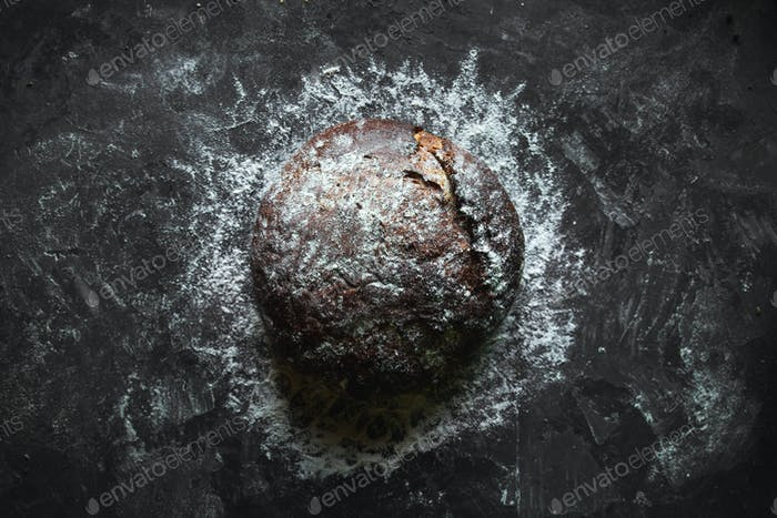 Black bread on a black background. homemade baking