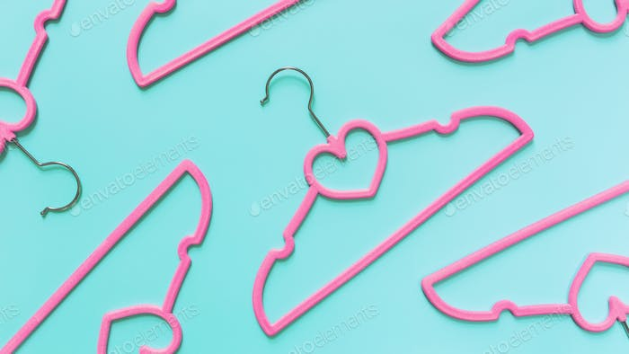 Black Friday or clothing industry concept on blue background with pink hangers