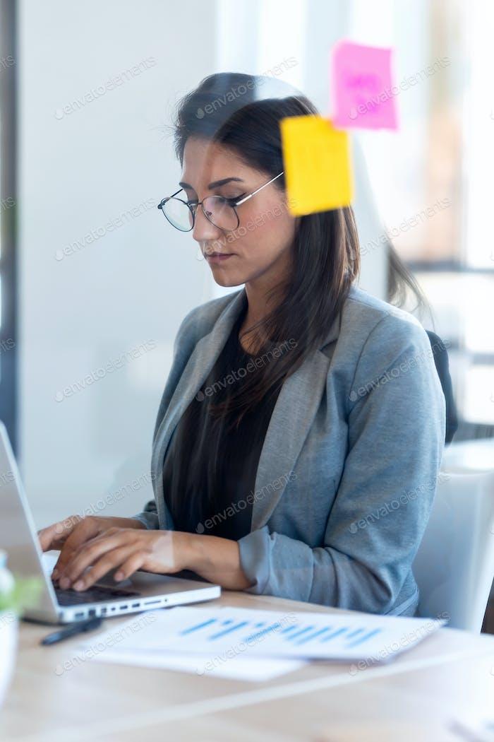 Konzentrierte Geschäftsfrau, die mit ihrem Laptop im Büro arbeitet.