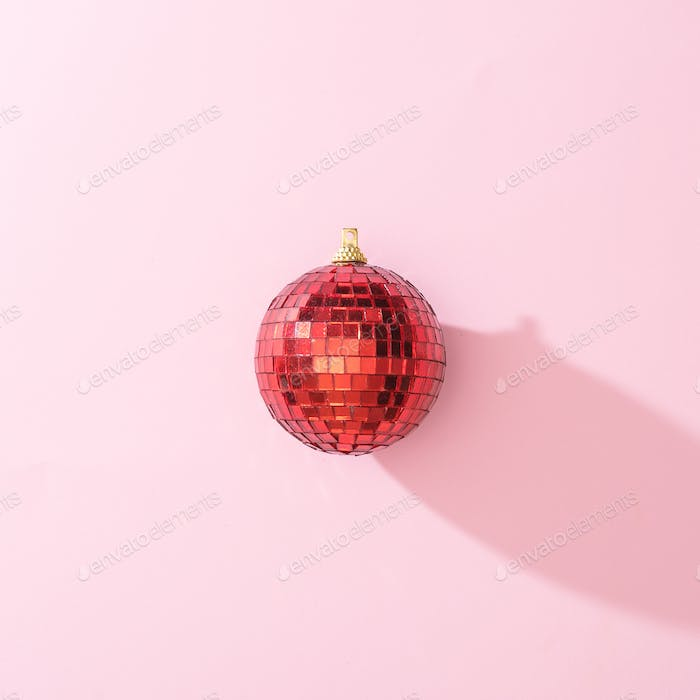 Red Christmas disco ball bauble on pink background. Minimal New year  party concept. Flat lay.