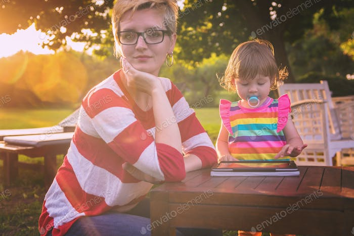 mom and her little daughter using tablet computer