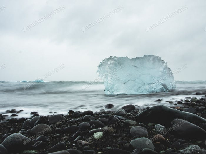 Iceberg being washed away on a black beach.