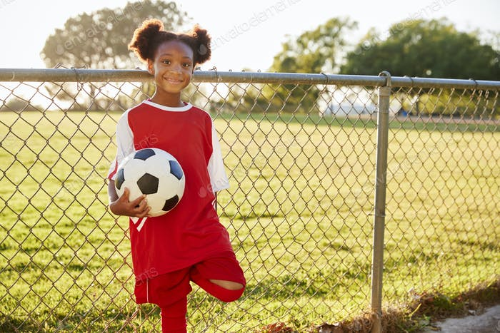 Pre teen black girl holding a soccer ball looking to camera
