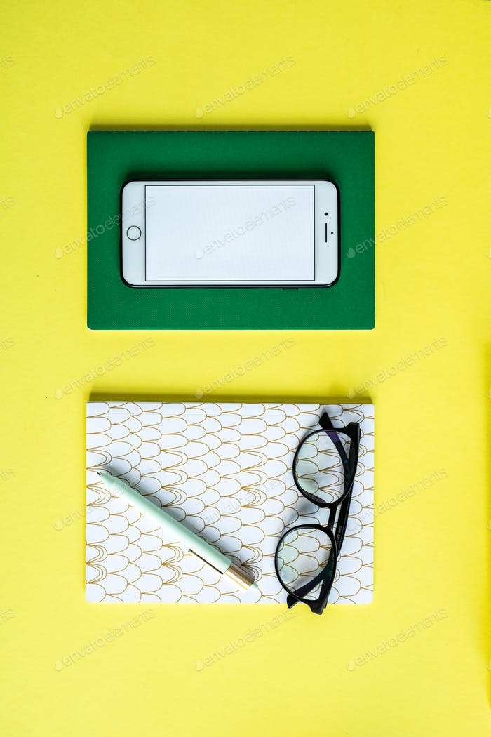 Smartphone on green notebook and pen with eyeglasses on copybook