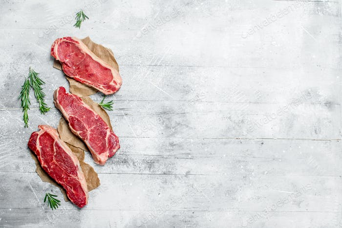 Raw marbled beef steaks with fragrant rosemary.