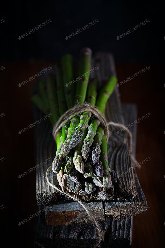 Bunch of fresh green asparagus spears on a rustic wooden table, dark moody style