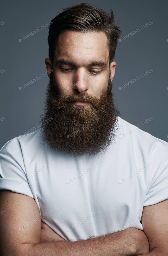 Bearded young man standing thoughtfully with his arms crossed