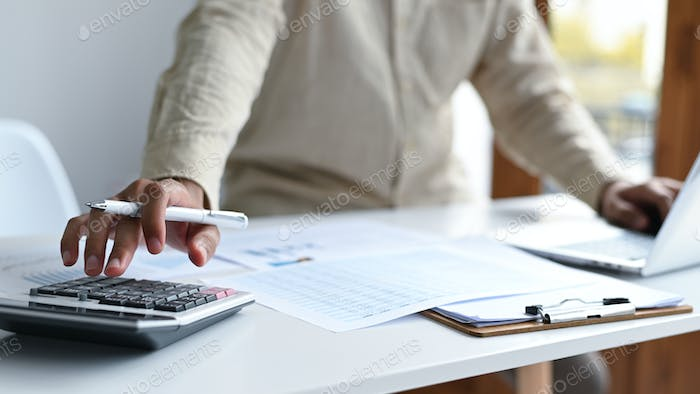 Hand with pen to use calculator and laptop keyboard, graphs and file folders on the desk.