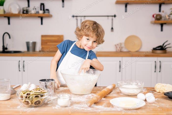 Niedlich und lustig kleine Junge zeigt in Schüssel, während gehen, um Teig zu machen