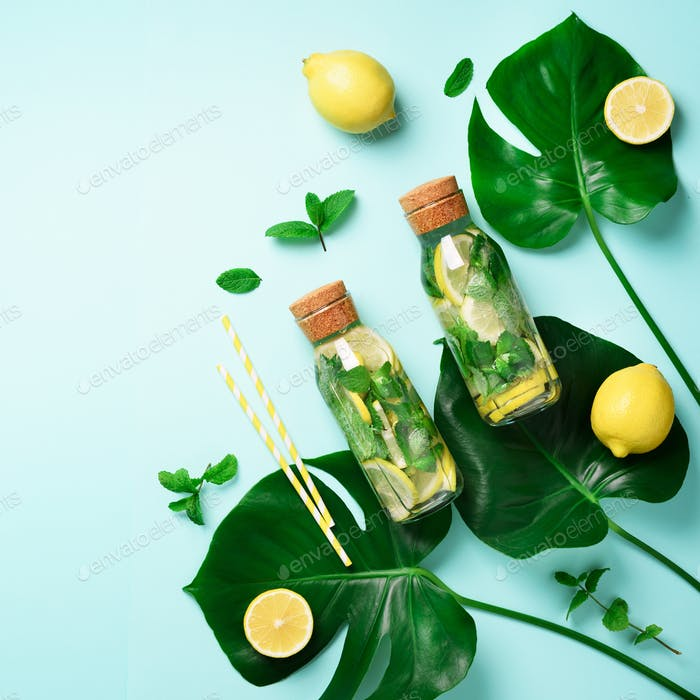 Bottle of detox water with mint, lemon and tropical monstera leaves on blue background. Square crop