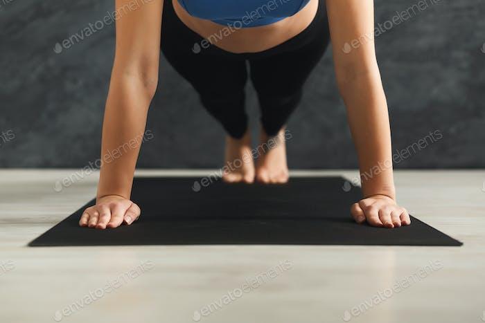 Unrecognizable woman training yoga in plank pose