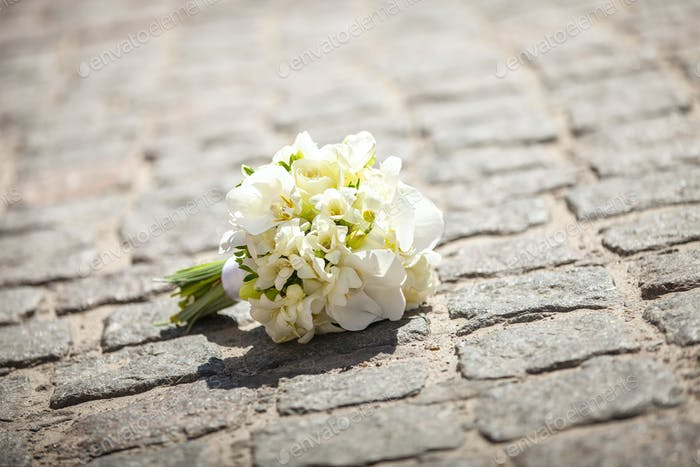 Bride's bouquet on paved road