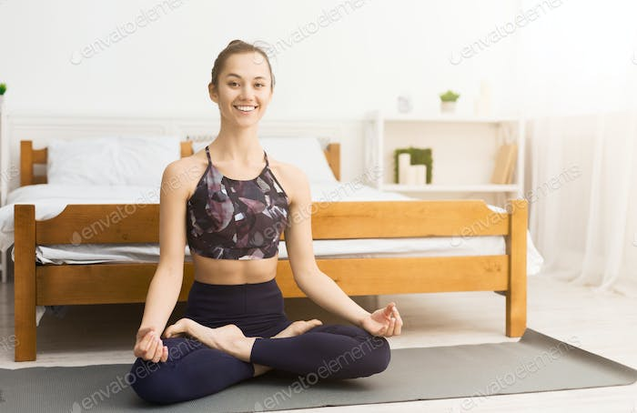 Happy fit woman enjoying yoga training at home