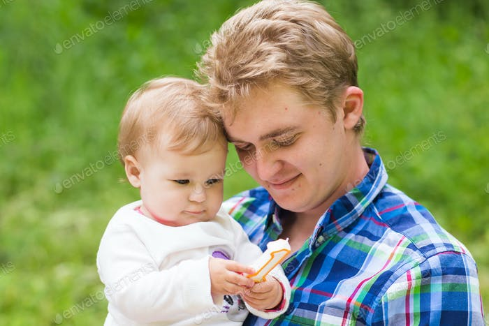 Portrait of happy father and his adorable little daughter in nature