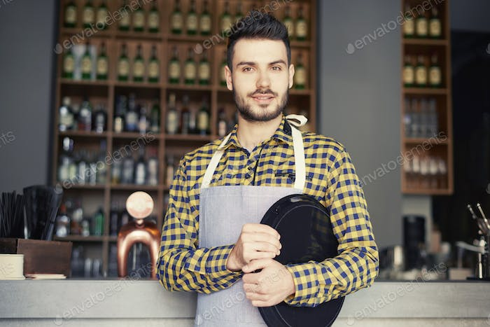 Portrait of man holding tray in th bar