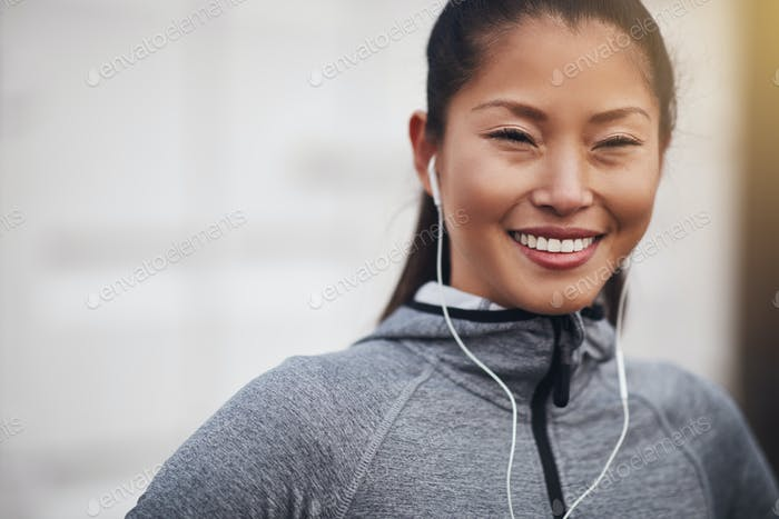 Sporty Asian woman listening to music on earphones before exercising