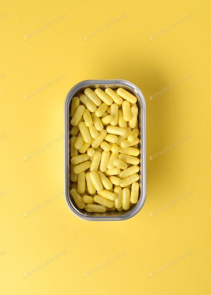 aerial view of group of yellow dragees in metal can