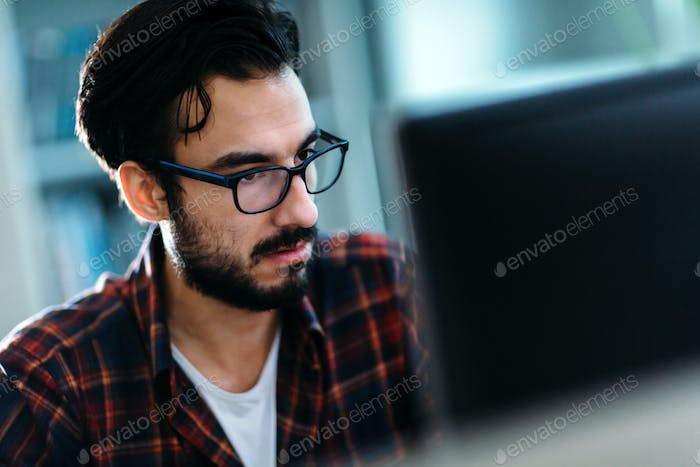 Portrait of young programmer working in office