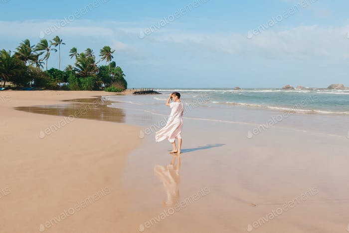 Woman legs walking on the beach sand