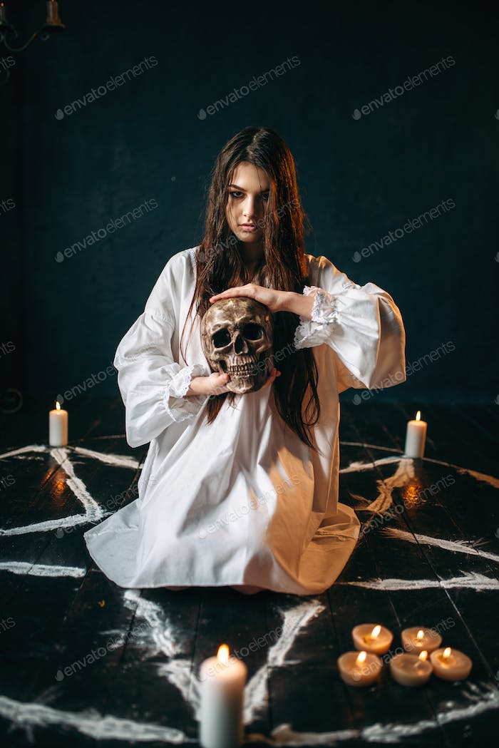 Woman holds human skull in hand, dark magic, witch